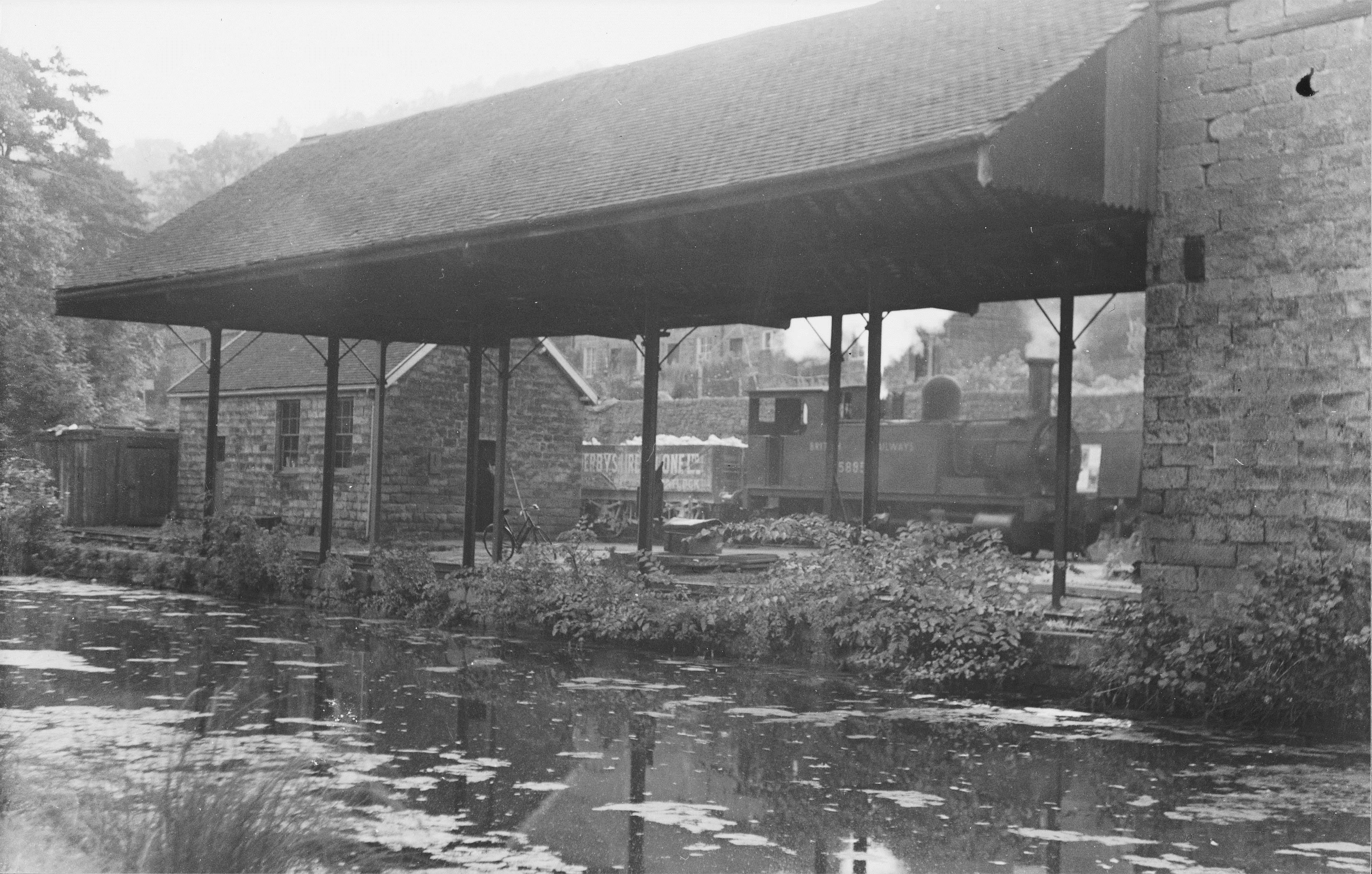 Taken on 10th October 1951, an engine shunts limestone wagons behind the Transhipment Warehouse with the Cromford Canal in the foreground.