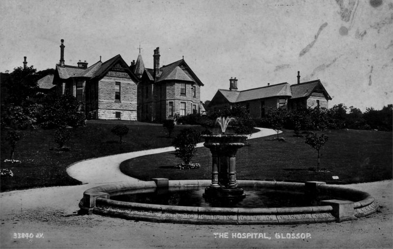 A black and white photograph of Wood's Hospital Glossop and the fountain in Howard Park