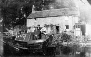 A narrow boat 'Thistle' infront of aqueduct cottage
